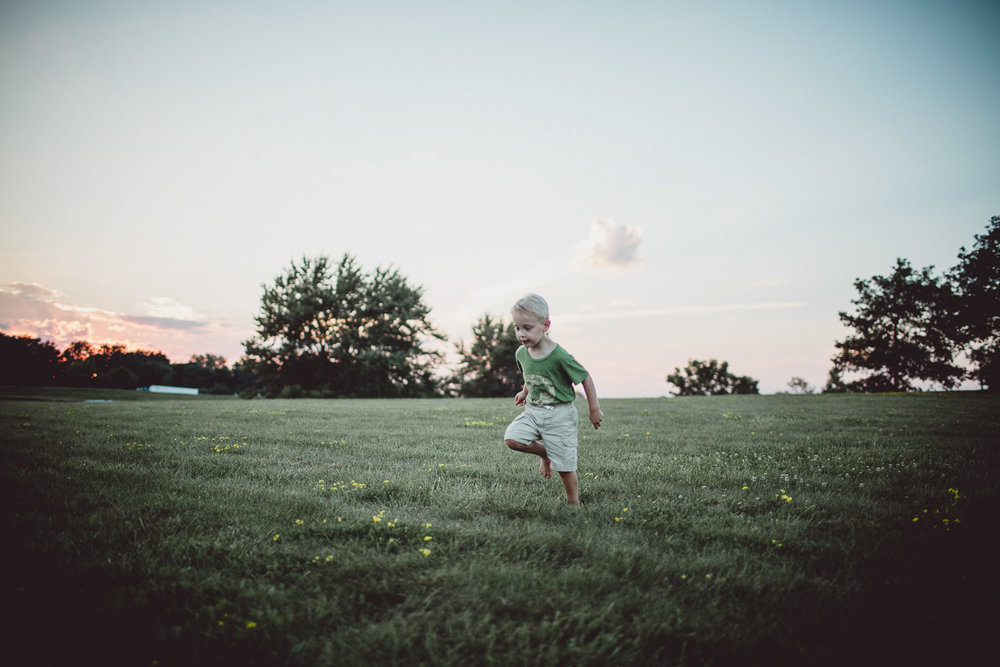 boy running through wide open field at sunset