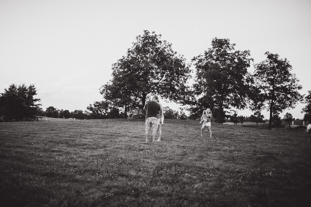 black and white portrait of family playing in field