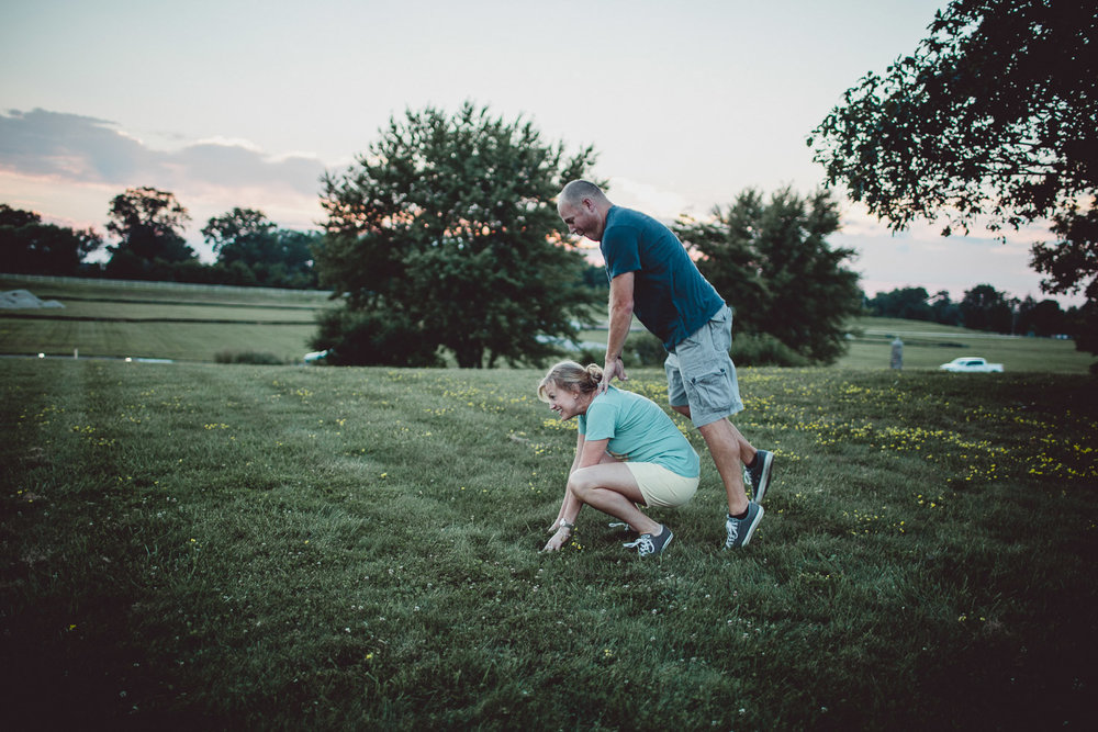 couple playing in leapfrog in field