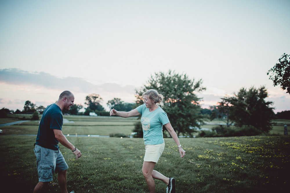 couple dancing playfully in field