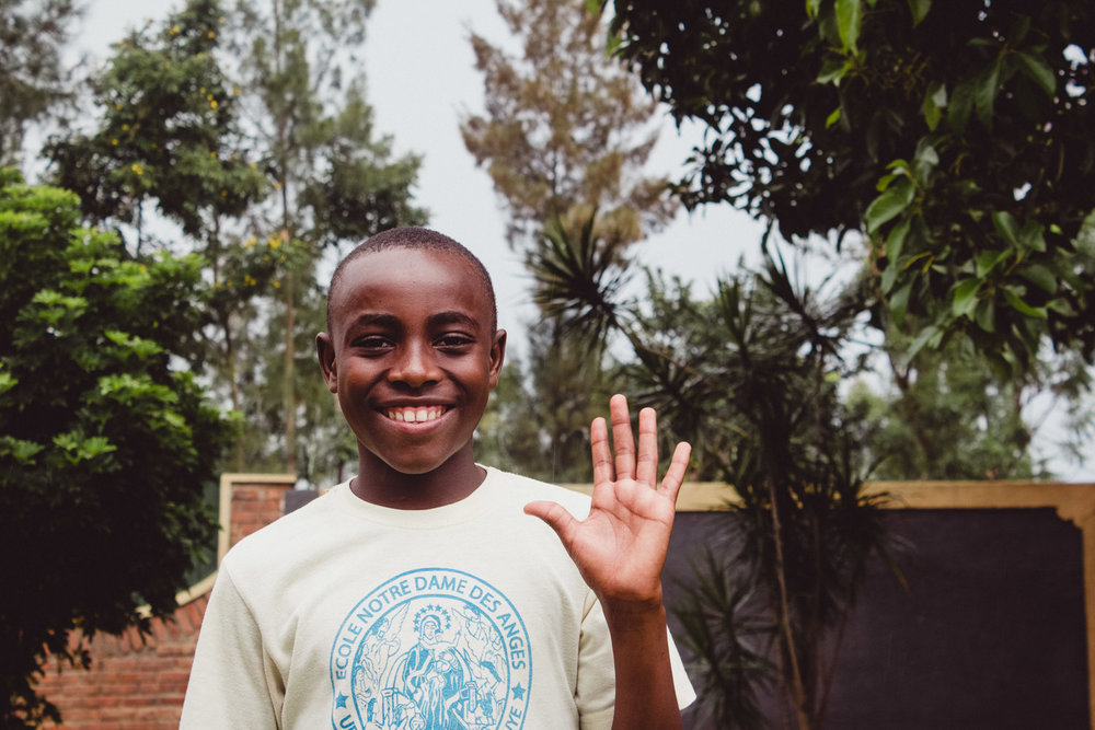 Student waving at an academy in Rwanda
