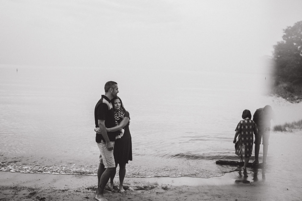 husband and wife hugging with children playing around them, black and white