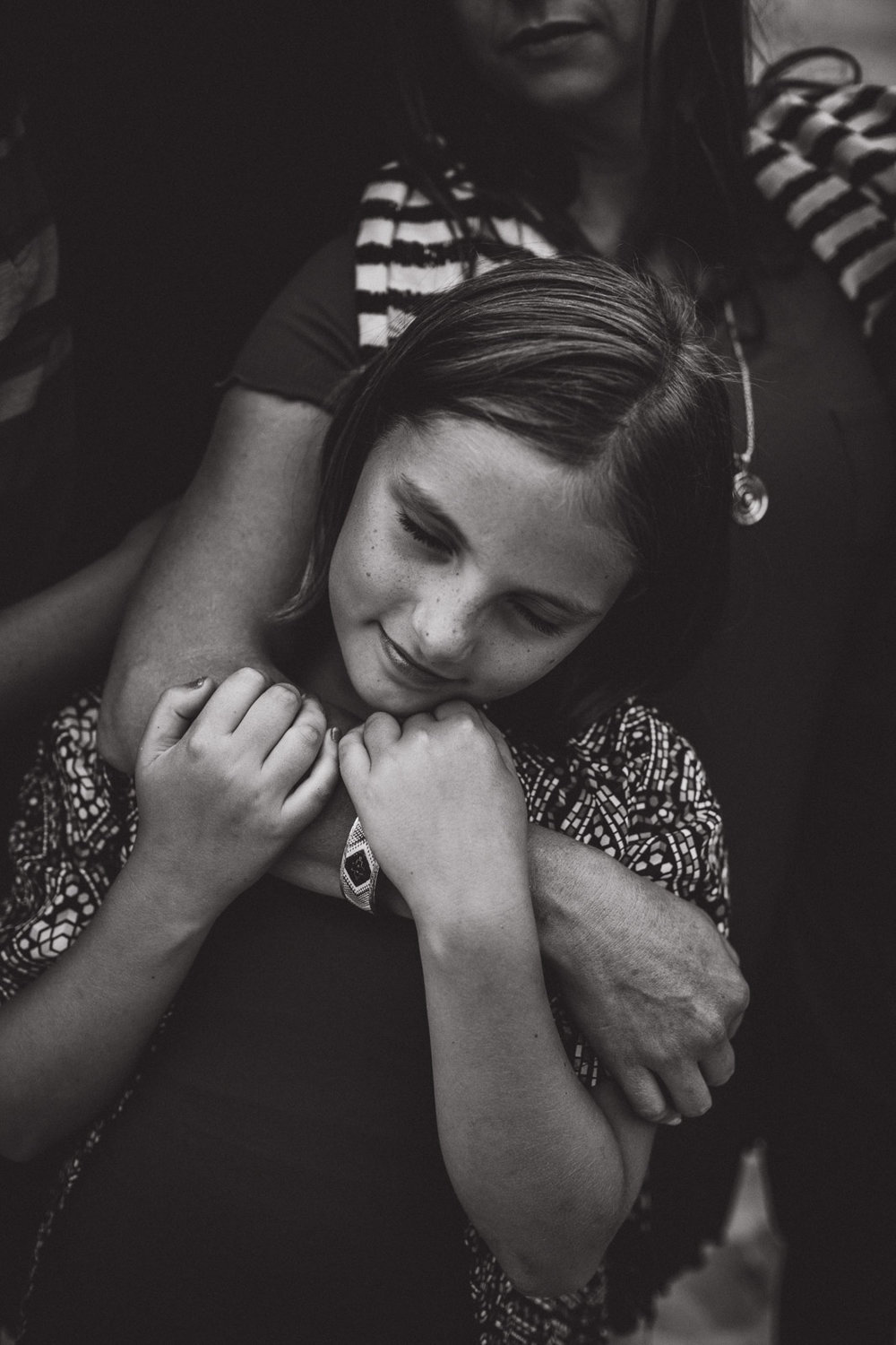 a girl wrapped tightly in her mothers arms