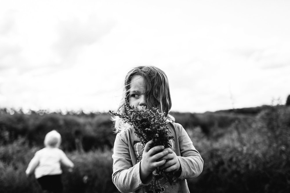 portrait of girl smelling flowers in field
