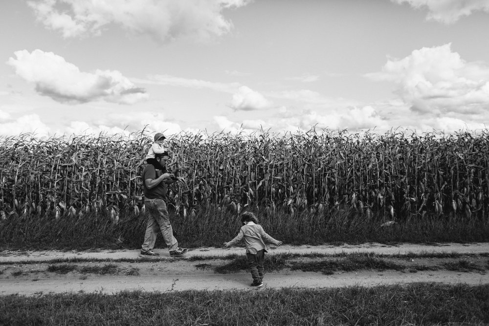 black and white portrait of family walking along field