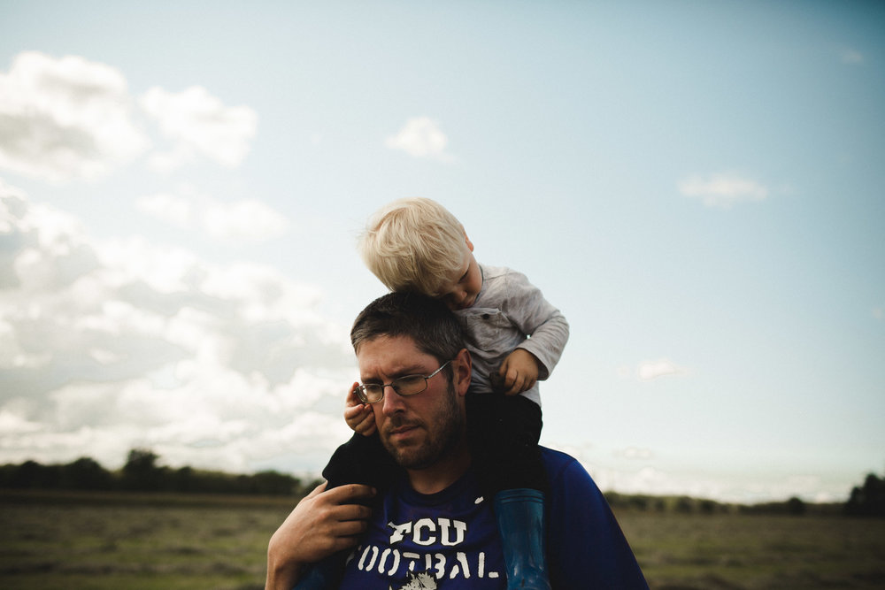 son hugging dads head while resting on his shoulders