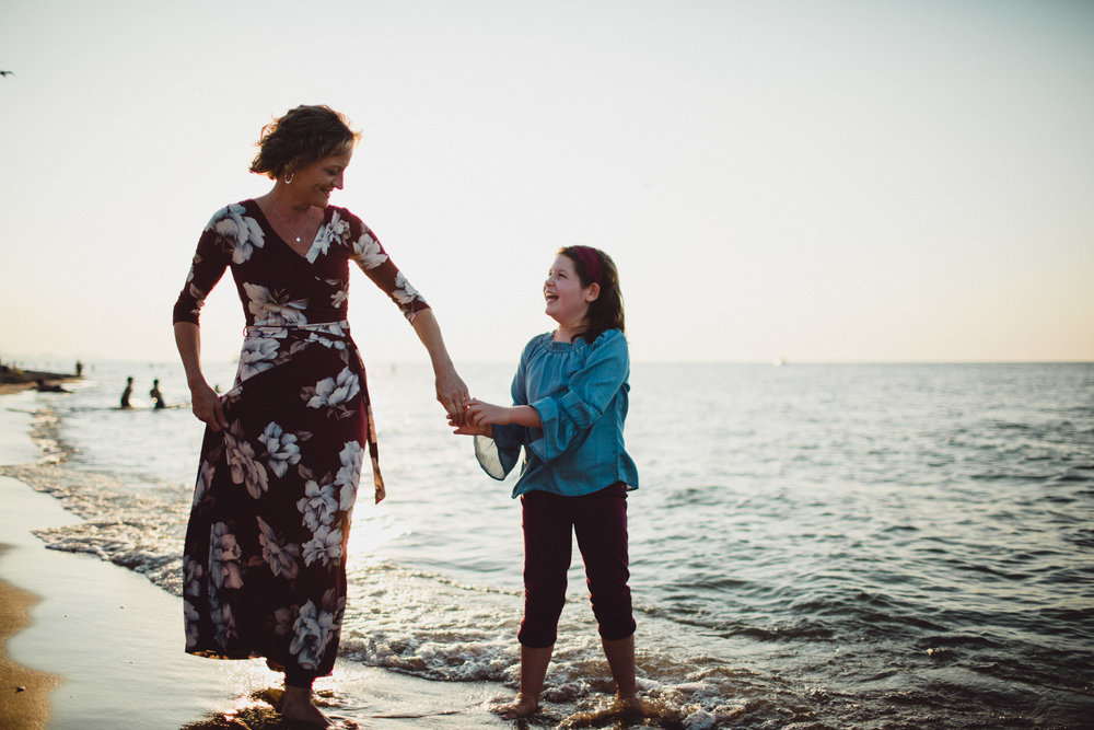girl dancing with her mother on the beach