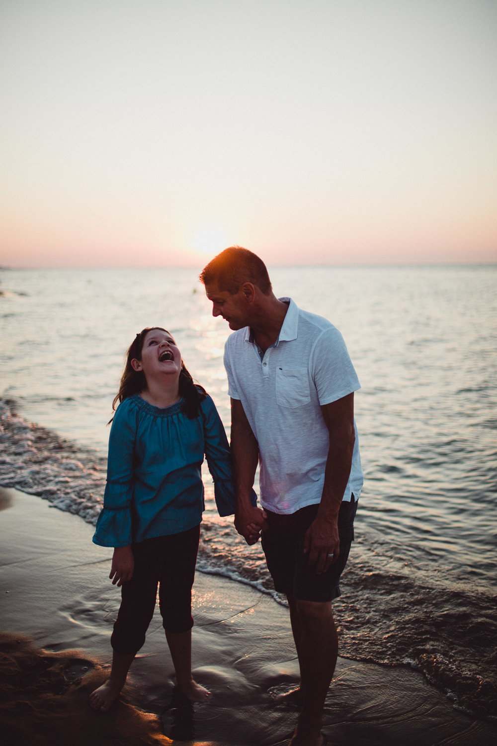 daughter laughing with her father on the beach