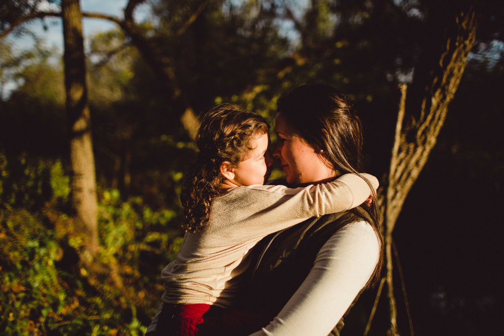 mother and daughter nuzzling noses in shadow light