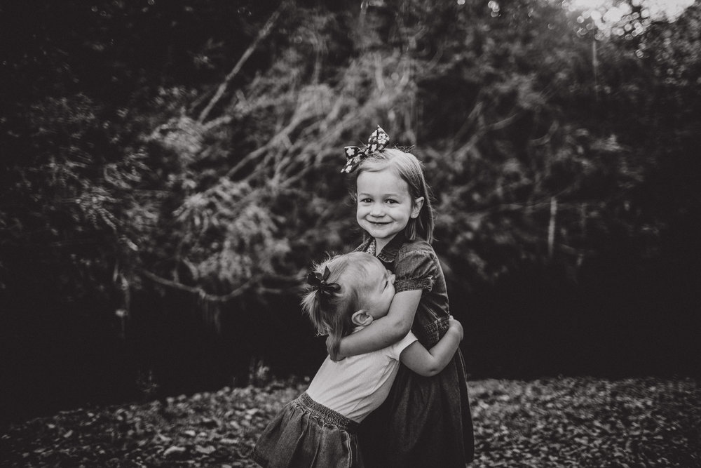black and white images of sisters hugging