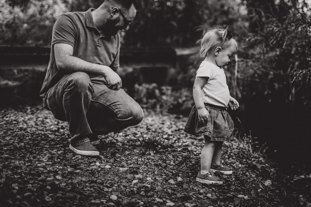 black and white image of father and daughter exploring creek together
