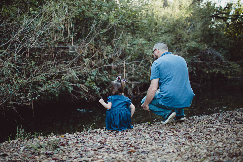 Image of father and daughter throwing rocks into the creek from behind