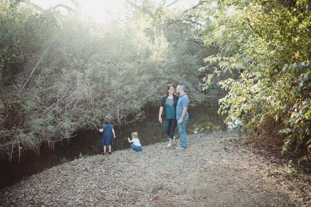 Image of family beside creek waters with light streaming in