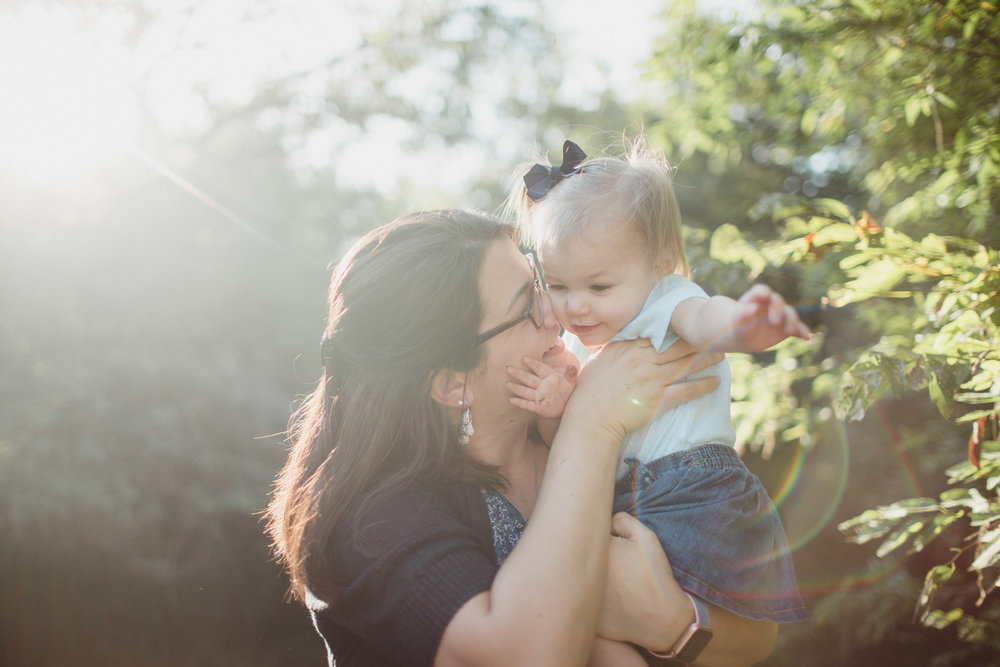 mother and daughter snuggling in beautiful sunflare light