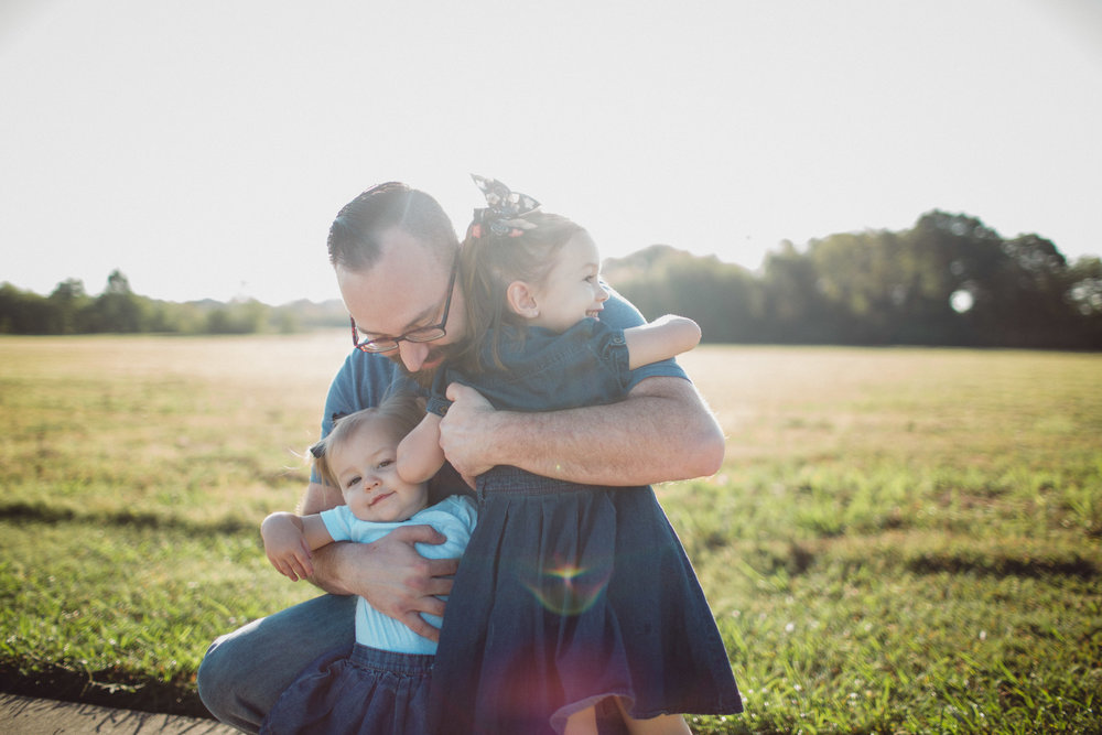 Father hugging his daughters with sun flare lighting
