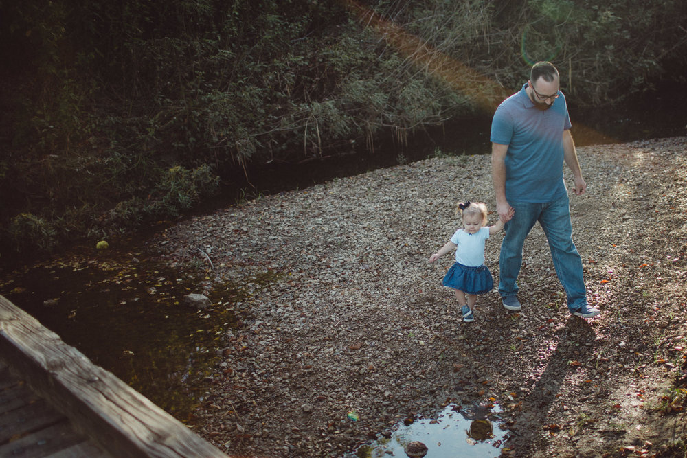 Father and daughter walking together beside creek