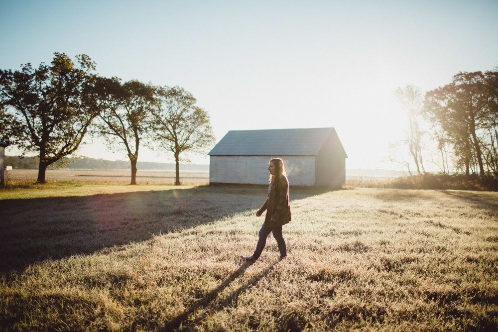 Mother walking across field, in dreamy morning light