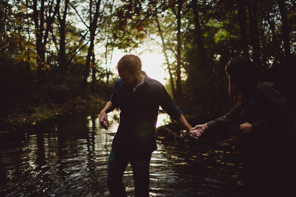 couple walking into beautiful creek with backlight