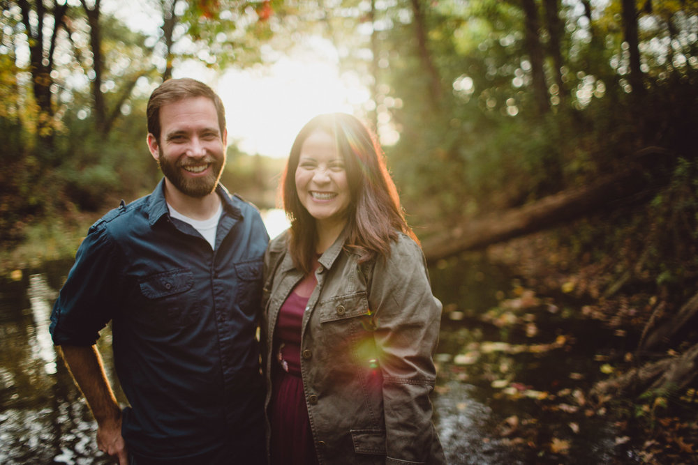 couple smiling with light flares in creek water