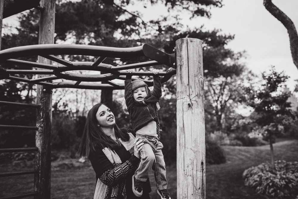 mother helping son across monkey bars