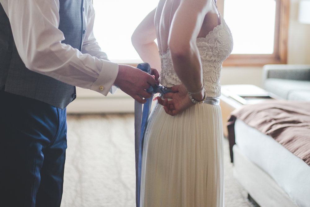 A groom helps his bride get ready for their breckenridge colorado winter elopement | photo by keeping composure photography