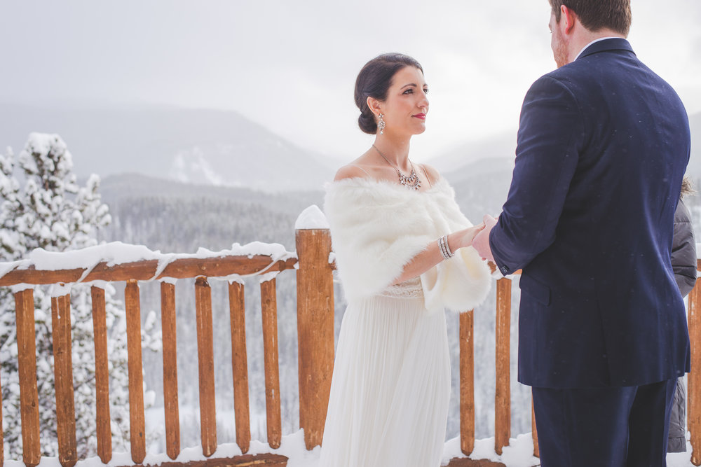 a classic bridal style for a winter wedding in breckenridge colorado: large earrings, tight low bun, red lips and a shawl to keep warm in the low temperatures | photo by keeping composure photography