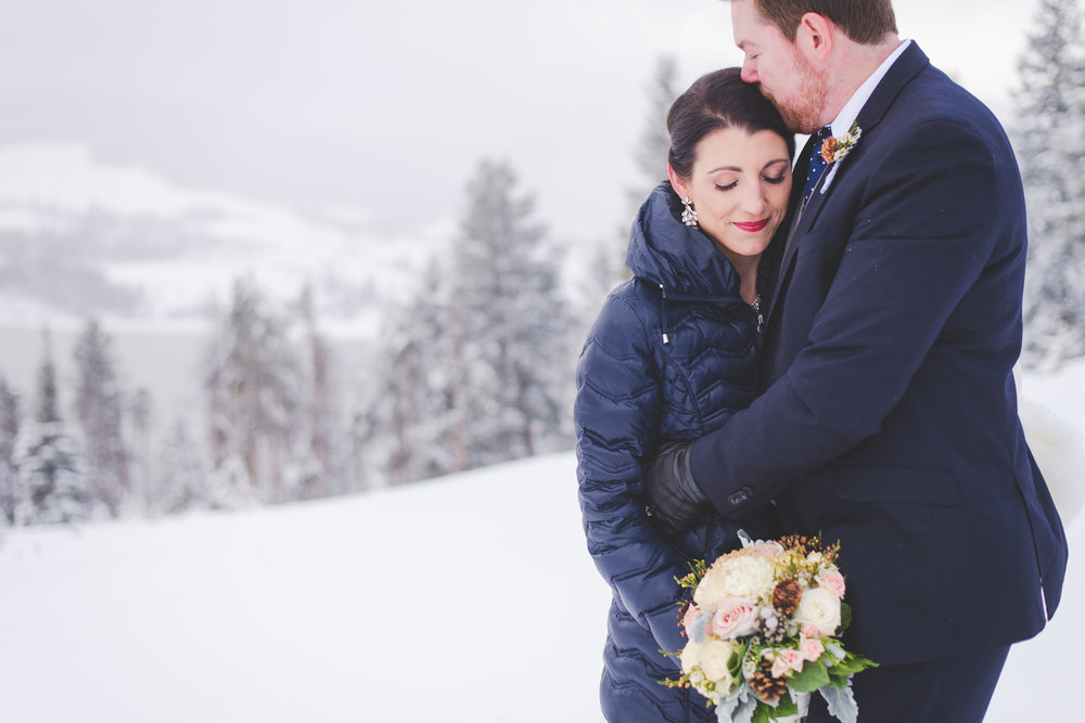 a sweet moment (and warm snuggles) between these newlyweds at sapphire point after their winter elopement in colorado