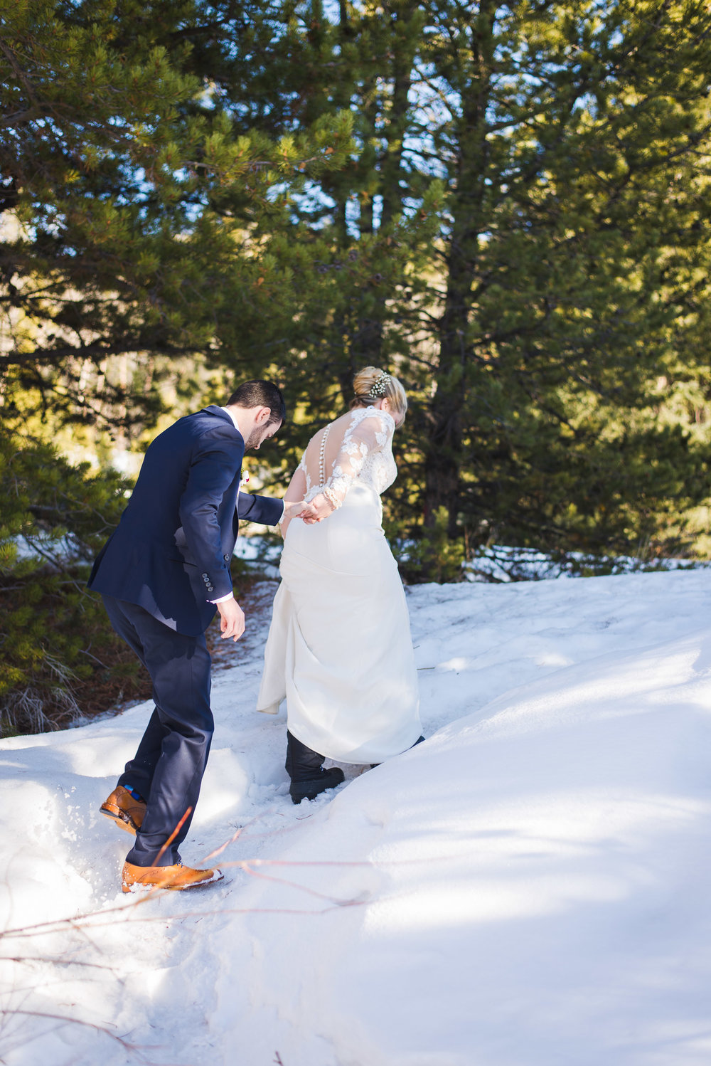 bride and groom hiking in snow