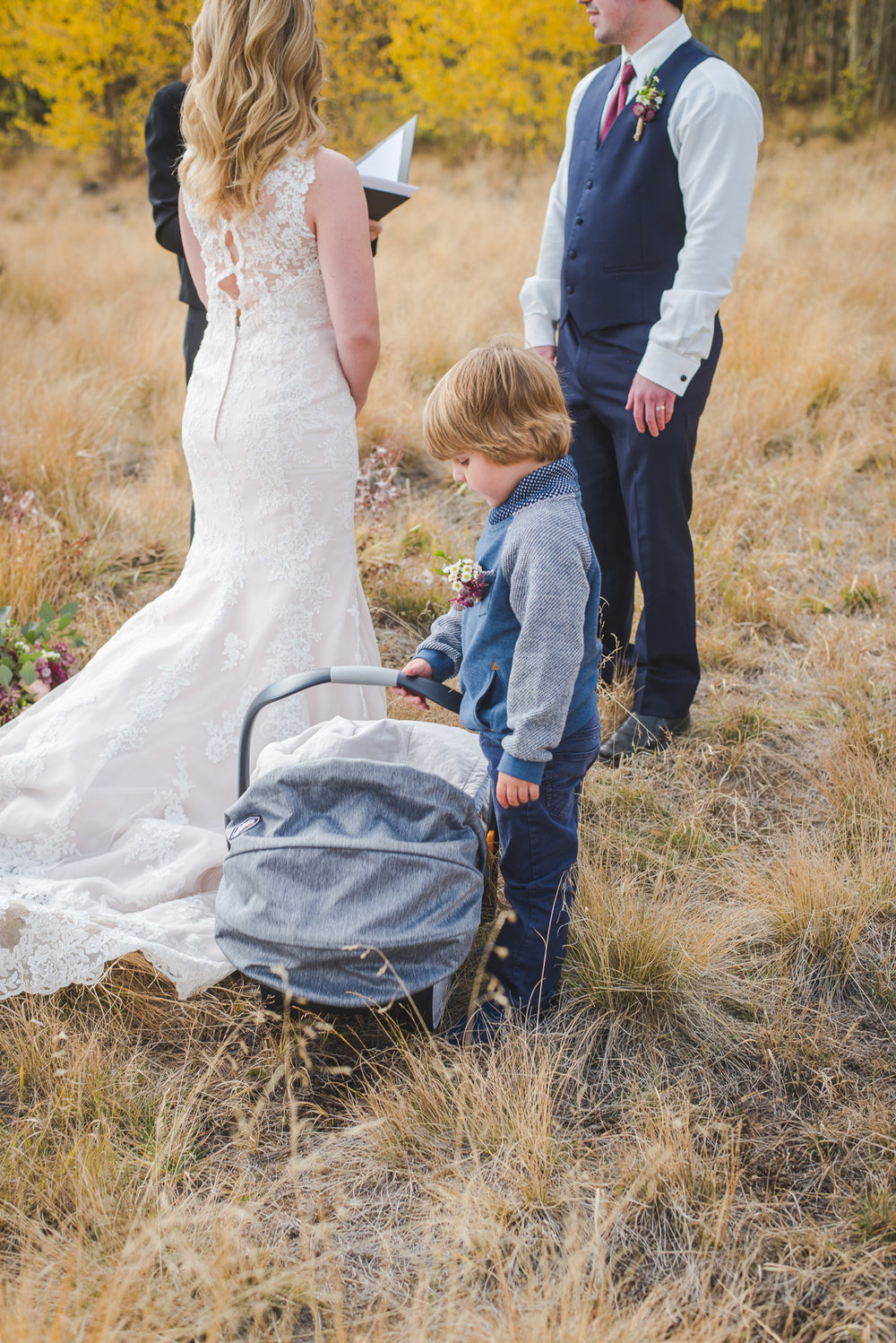 Autumn elopement in Breckenridge, Colorado | Young boy watching over his younger baby brother at ceremony | Summit Mountain Weddings