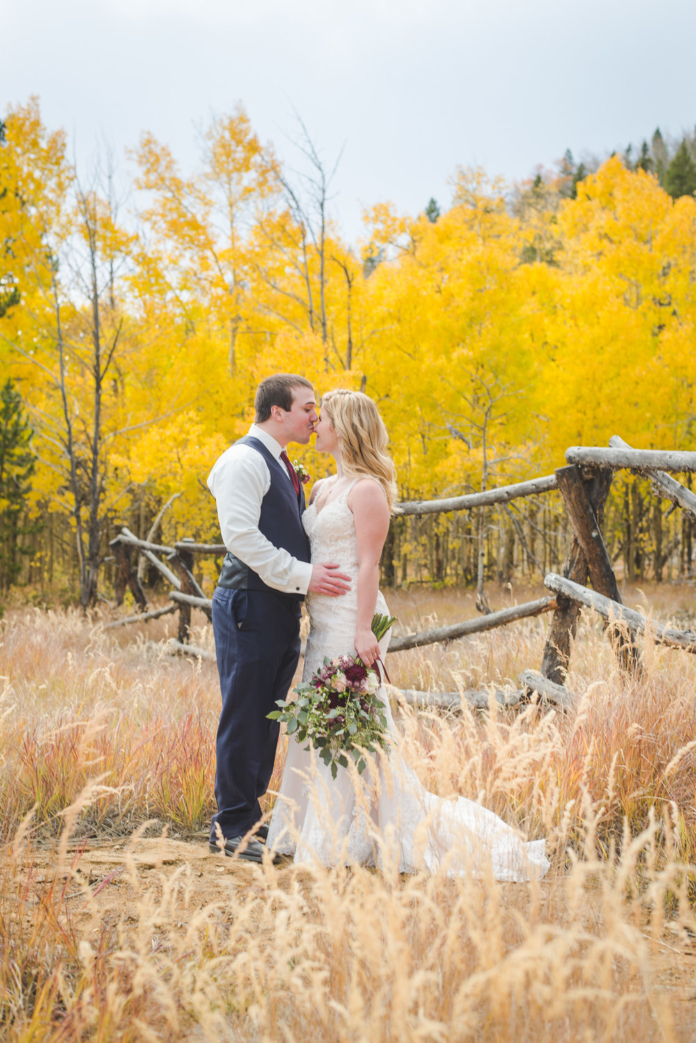 Bride and groom in front of wood fence and yellow trees | Autumn elopement in Breckenridge, Colorado | Summit Mountain Weddings