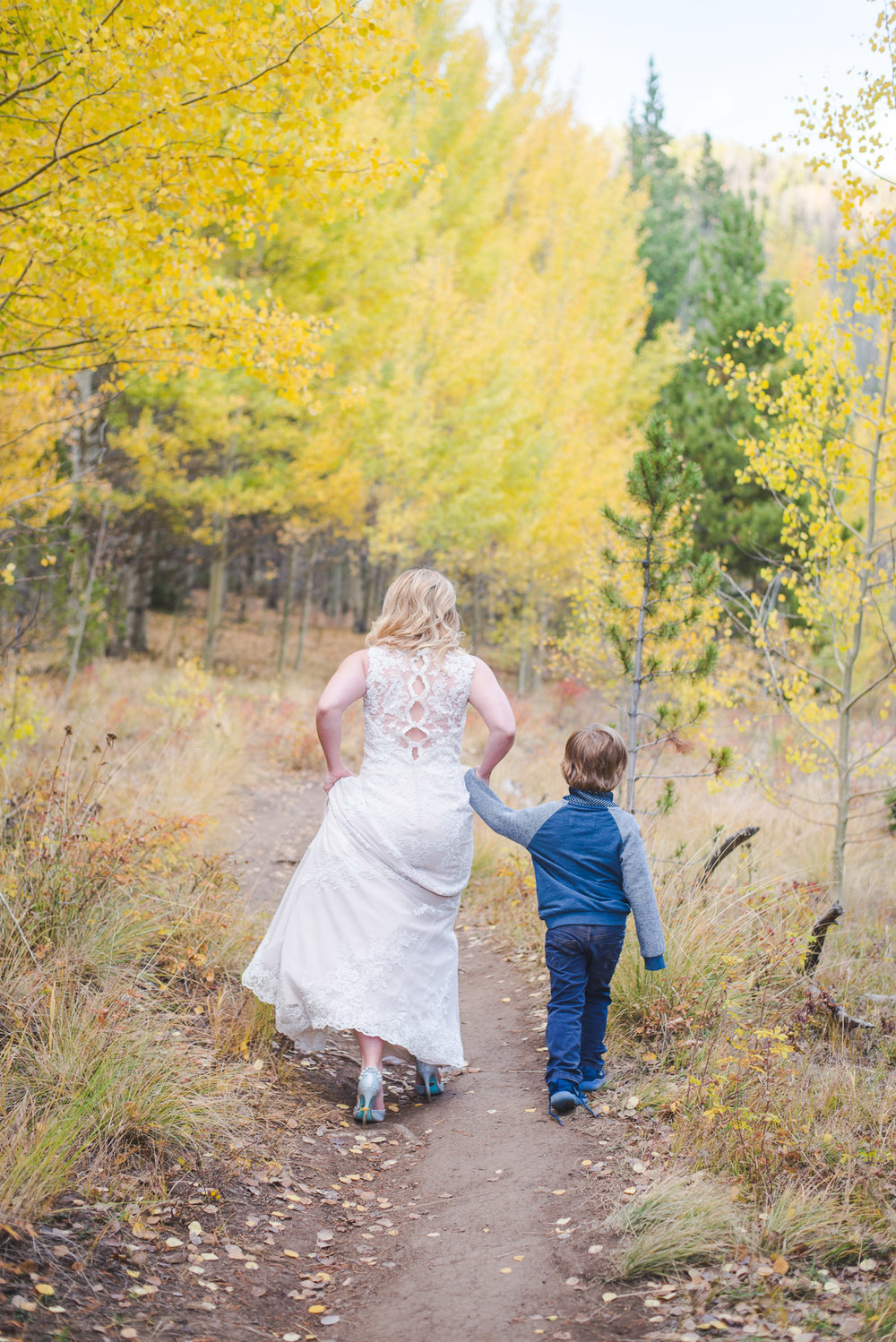 Walking away with young boy - mom and bride in one day | Autumn elopement in Breckenridge, Colorado | Summit Mountain Weddings