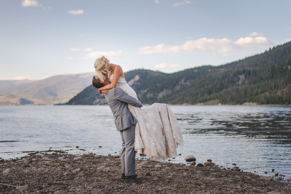 bride and groom kiss by lake