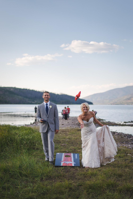 bride and groom cornhole by lake