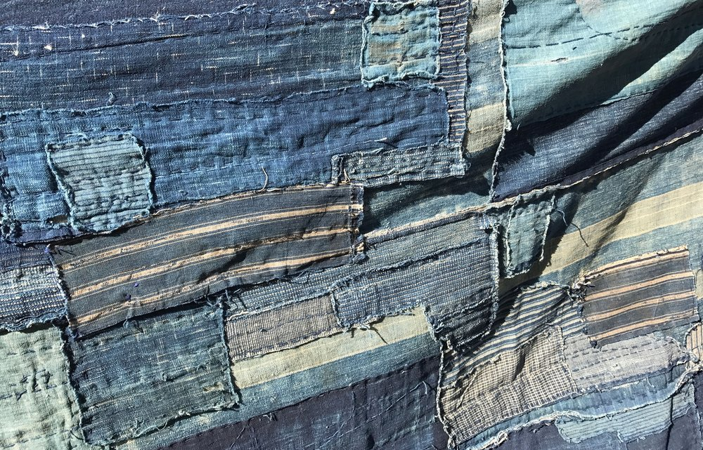 'Boro' fabrics are old Japanese fabrics with patches. They are mostly dyed with indigo and are nowadays sought-after collector's items found in museums and used as tapestery