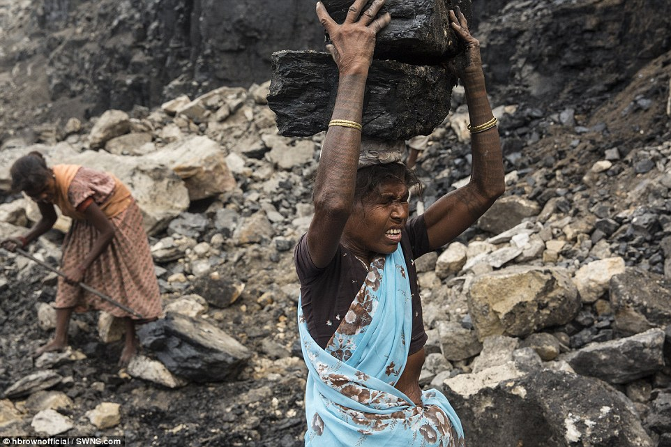 A woman - an illegal coal scavenger - hauls a heavy block of coal out of an operating open-cut coal mine in eastern India. She is a member of India's Adivasi indigenous people, working in Jharkhand