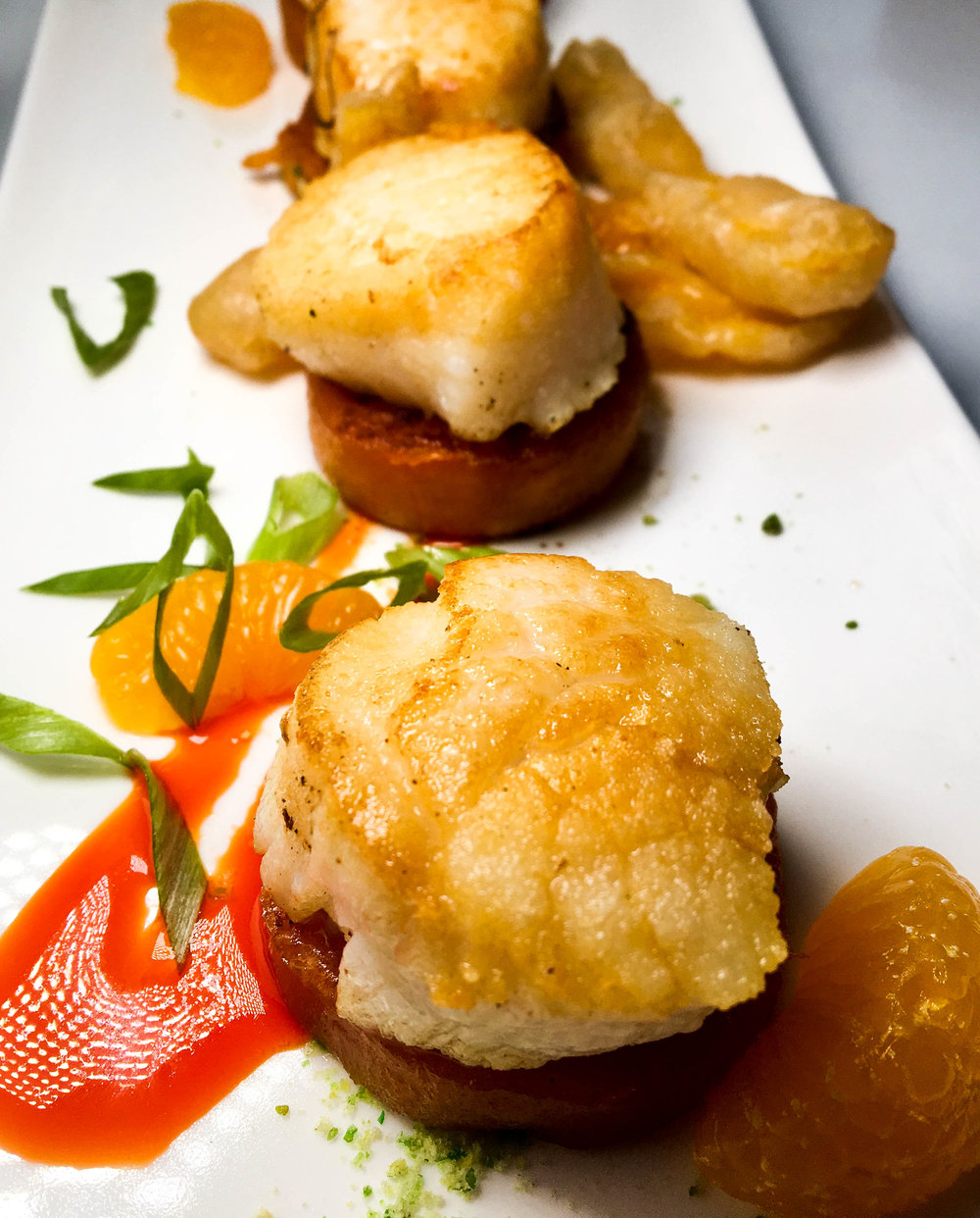 Pan seared scallops with wasabi pea dust, sweet potato fondant, mandarin oranges, and tempura fried mango in a blood orange coulis.