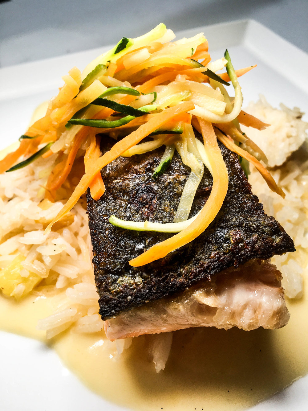 Pan seared salmon with pineapple basmati rice, lotus chips and summer slaw in a white chocolate beurre blanc.