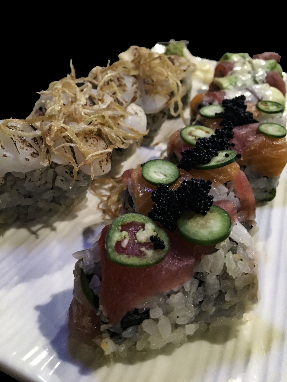 Left - Port Washington Roll - Crunchy spicy king crab topped with seared scallop, onion and yuzu truffle soy  Right - Kiss of Fire Roll - Crunchy spicy yellowtail topped with tuna, salmon,  jalapeño, and fish eggs