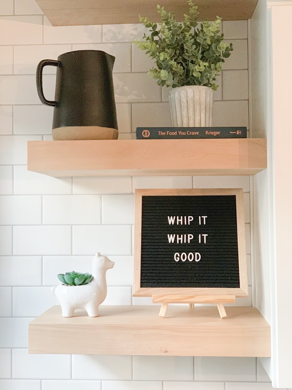 floating shelves on white subway tile and letter board