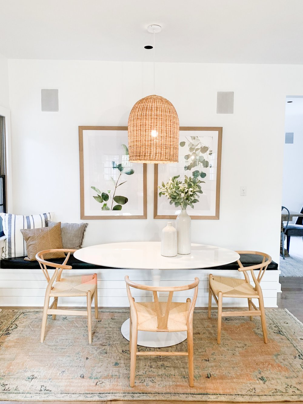 pendant light over white oval table and wishbone chairs