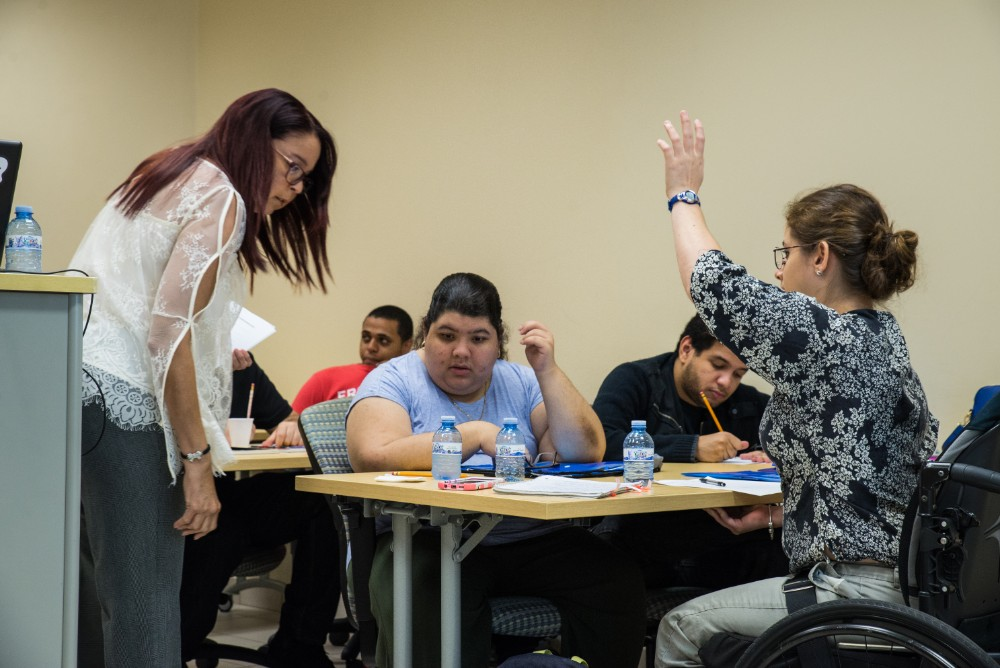 "A student raises her hand to answer a question during a Leadership Academy lesson on ""Sunshine Laws"""