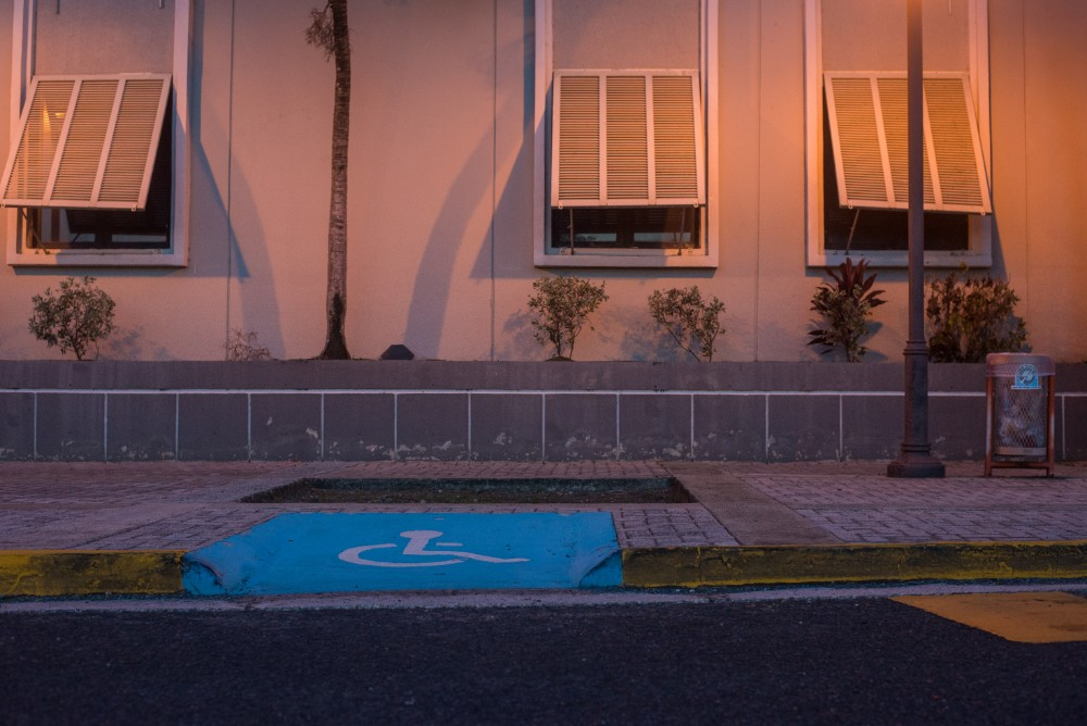 A curb cut leads to the entrance of the San Juan Port Authority building.