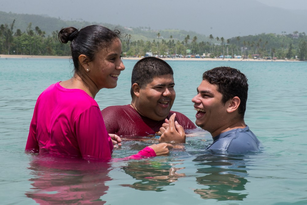 Camp MAVI clients laugh together while swimming at Luquillo Beach.