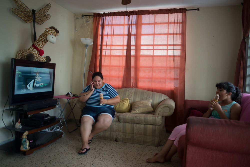 6/9/18 – Bayamón, Puerto Rico – Crystal is a student in the fourth grade at Aurelio Perez Martinez, one of the schools set to close before the Fall. They live on the same block as her current school, and will have to commute in a school bus that arrives early in the morning to pick up the kids if they are relocated to a new school because the family does not own a car. She sits at home one Saturday afternoon with her mother, Nancy Rodriguez, an active community member of Aurelio.The Puerto Rican Department of Education is closing 283 schools, and moving multiple schools into the same building, citing the past year's drastic drop in enrollment as one of the primary reasons to lower the amount of schools, and instead increase the amount of students in each school. Students of special education schools are one of the groups to be most negatively affected by these closings, as the new schools may not offer the resources the students need and have access to at their current schools. (Sofie Hecht Photography)