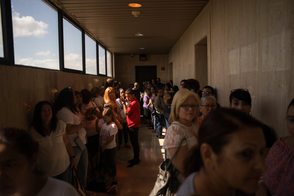 6/11/18 – Arecibo, Puerto Rico – Families and teachers of schools that are to be closed before the Fall 2018 academic year wait in the Judicial Center of Arecibo for the public hearing from the Department of Education about their reasonings for closing schools.The Puerto Rican Department of Education is closing 283 schools, and moving multiple schools into the same building, citing the past year's drastic drop in enrollment as one of the primary reasons to lower the amount of schools, and instead increase the amount of students in each school. Students of special education schools are one of the groups to be most negatively affected by these closings, as the new schools may not offer the resources the students need and have access to at their current schools. (Sofie Hecht Photography)