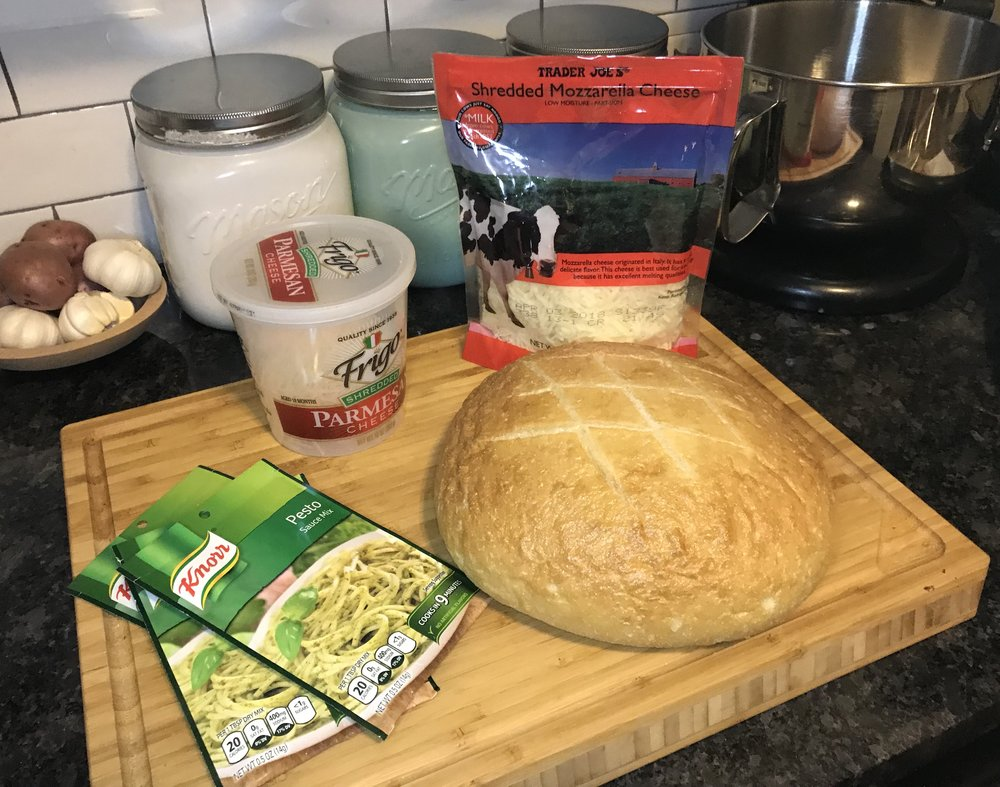 Ingredients  - 1 medium-large round or oval loaf of bread3 packs Knorr Pesto Mix (you can buy find these at the grocery store by the sauce/sauce mixes)1/2 cup Olive Oil2 cups white cheese (half mozzarella and half parmesan)