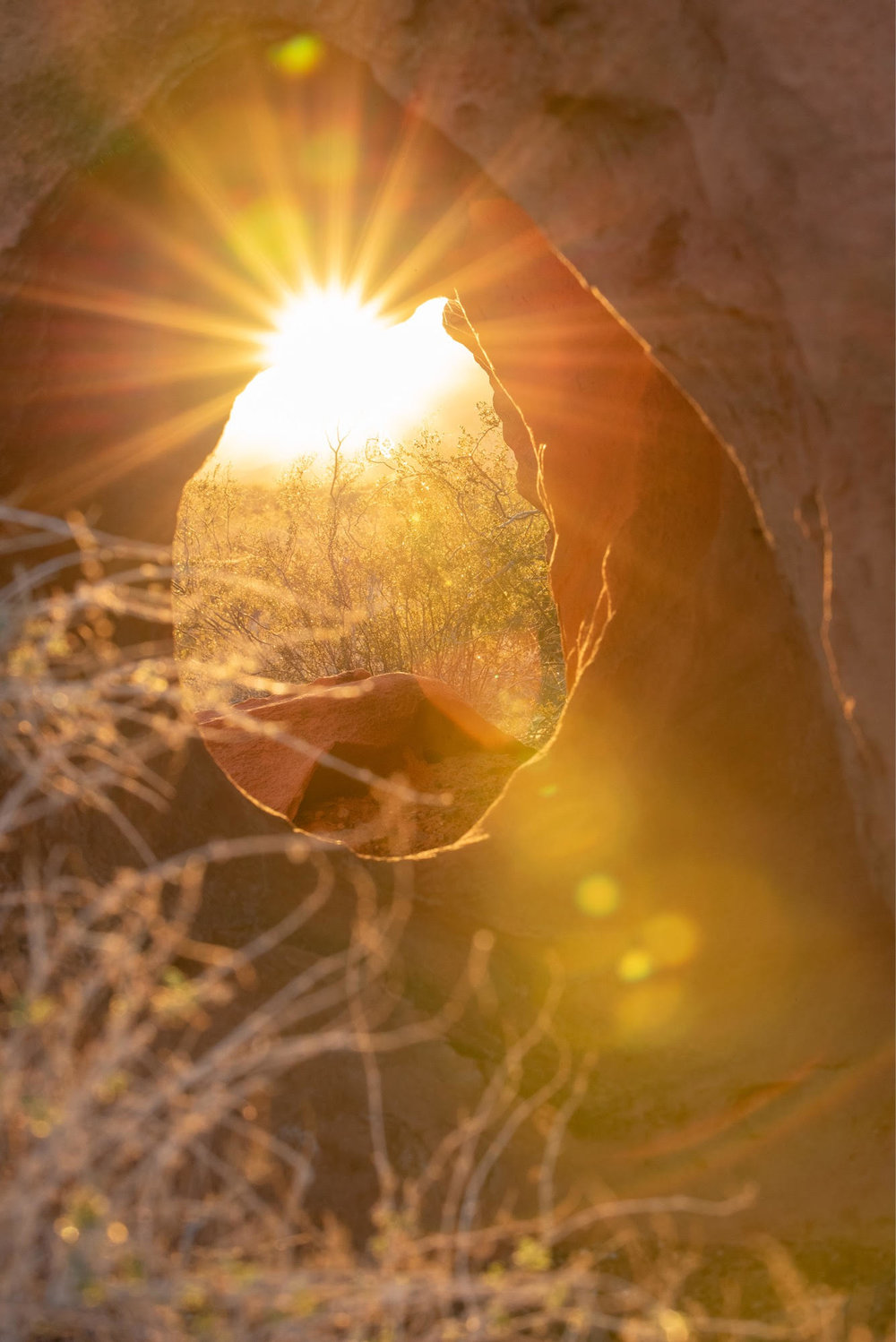 I took this in early November, and loved capturing the sunburst through the hole in the red rocks.