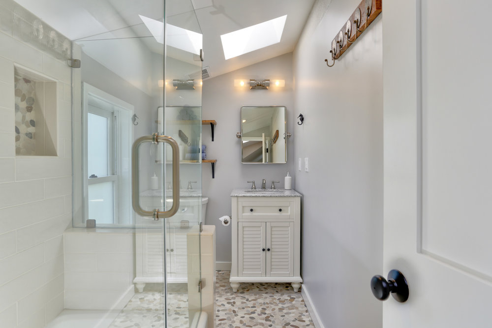 NEW: Beachy themed bathroom with pebble floor, oversized subway tiles and wood accents.