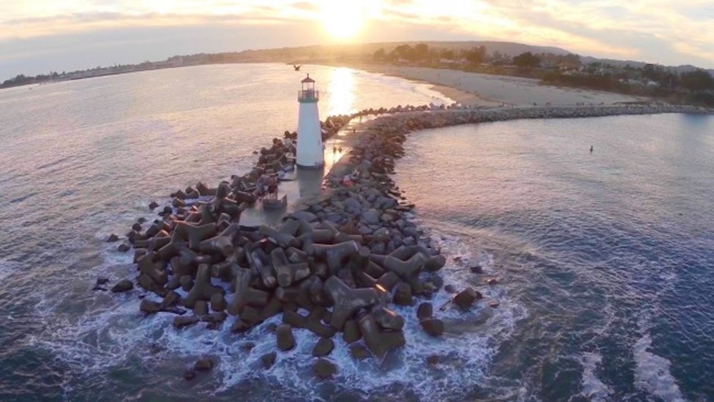 """Walton Lighthouse atop the west jetty with its distinctive huge cement """"tetrapods."""""""