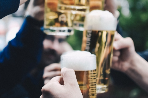Young male hands hold beers in cheers gesture outdoors in summertime